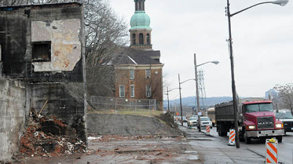 The demolished Allegheny Auto Body leaves St. Nicholas Church as the last structure standing along East Ohio St. on Pittsburgh's North Side. Demolition preparations are ongoing inside the church.