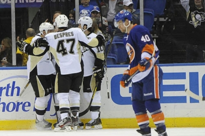 The Penguins' Craig Adams, Simon Despres and Tanner Glass celebrate Joe Vitale's goal as the Islanders' Michael Grabner skates away in the second period.