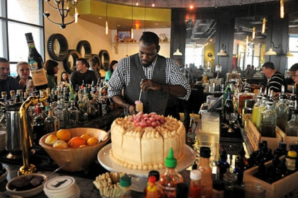 Bartender Cecil Usher mixes drinks for the packed brunch crowd at Meat and Potatoes, Downtown.  The cake in front of him is a peanut butter-raspberry jam cake.
