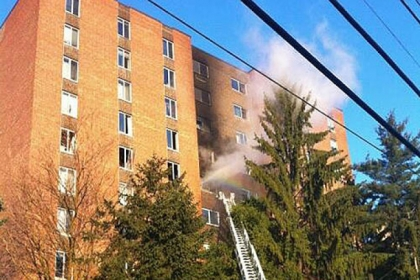 Smoke pours from the building as crews battle the fire this morning in the nine-story Amberson apartment complex on Bayard Road. A man died in the fire.