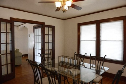 Dark-stained French doors connect the dining room and the living room.
