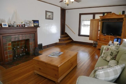 The living room in this two-story Colonial in Washington has a hardwood floor. The decorative fireplace has an original tile surround and hearth topped by a beautiful Craftsman-style wood mantel.