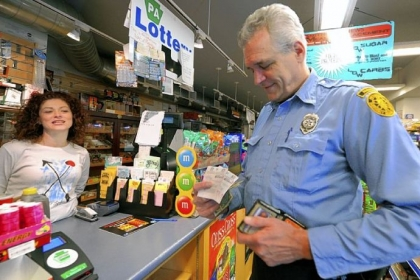 Jack Winterbottom, a Pittsburgh paramedic with Rescue 2, buys his lottery tickets from cashier Antoinette Sciulli at Smithfield News, Downtown.