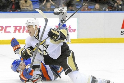 Pascal Dupuis collides with the Islanders' Andrew MacDonald Friday at Nassau Coliseum  in Uniondale, N.Y. Dupuis scored an empty net goal in the Penguins' 4-2 win.