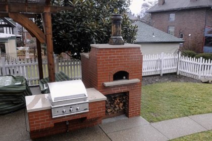 Backyard cooking area including a pizza oven.