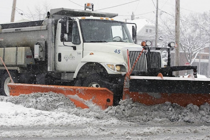 A snow plow moves wet, slushy snow from an intersection in Rockford, Ill., today, as a winter storm headed for Pittsburgh blew through that area.