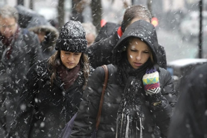 Commuters brace the snow as they arrive in downtown Chicago this morning. The Windy City was expecting as much as 10 inches of snow from a storm that will head toward western Pennsylvania tonight.
