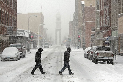 Pedestrians cross Main Street in Dubuque, Iowa during heavy snow today. The storm is headed toward western Pennsylvania.