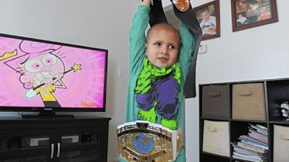 "Connor Michalek, 7, shows off his wrestling belts at his Hampton home. Wrestling is an ""everyday, all day activity,"" for him and his brother, Jackson, according to their mother, Brittany Caligiuri."