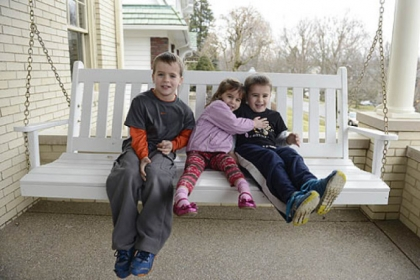 Ben, 7, Maria, 4, and Sam McAuley, 5, rock in the swing on their new front porch in Mt. Lebanon.